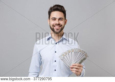 Smiling Young Unshaven Business Man In Light Shirt Posing Isolated On Grey Wall Background. Achievem
