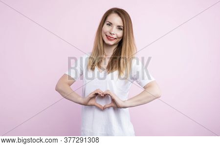 Picture Of Cheerful Beautiful Charismatic Female Looking Directly At Camera, Making Gesture, Showing