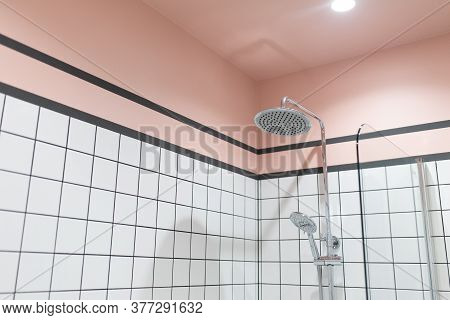 Closeup Image Of Shower And Shower Head In Modern Bathroom With White Tiles And Pink Walls And Ceili
