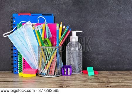 School Supplies And Covid 19 Prevention Items On A Desk Against A Chalkboard Background. Back To Sch
