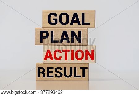 Wooden Blocks Form The Words Goal, Plan, Action, Result On Blue Background. Male Hand.