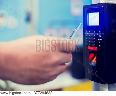 Door Access Control. Selective Focus To Card Reader Machine With Blurry Staff Holding A Key Card To