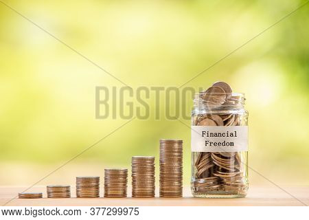 A Glass Jar Filled With Coins Placed Beside A Pile Of Coins. Saving Money For Financial Independence
