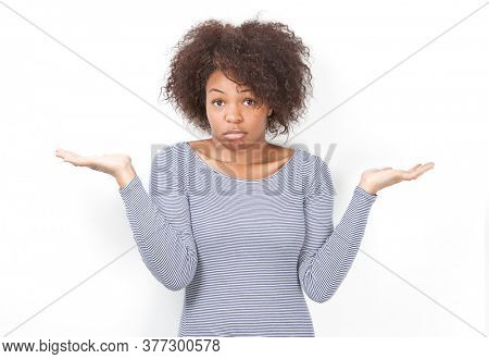 Portrait of confused African American young woman shrugging against white background