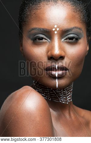 Portrait of young african american woman with traditional white paint on face