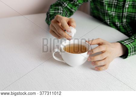 A Person Hand Holding Some Sugar Cubes And Put Them Into Cup Of Tea Sitting At The Table