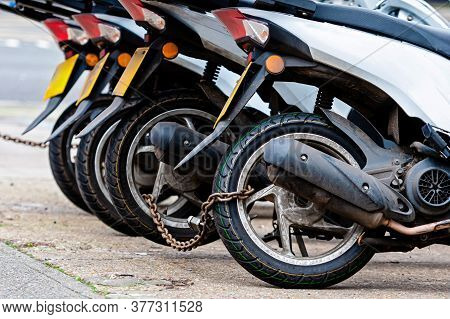 The Rear Wheels Of The Pizza Delivery Scooter Chain Are Locked With An Anti-theft Chain - Image