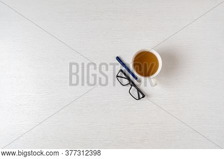 A Top View Of A Simple Desk Office Table Desk Workplace With Hot Cup Of Tea, Pen And Glasses, Copy S