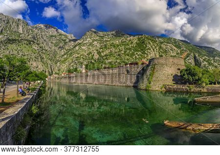 Kotor, Montenegro - May 30, 2019: Emerald Green Waters Of Kotor Bay, Mountains And The Ancient Stone