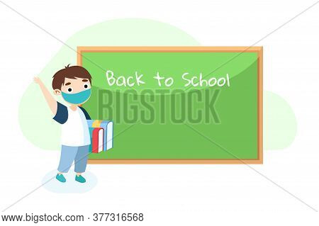 Boy In Medical Mask With Books Stand In Classroom Near Blackboard Waving Hand. Back To School During
