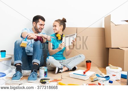 Happy Couple Watching Something Funny On Tablet Computer While Sitting On Floor. Painting Tools And