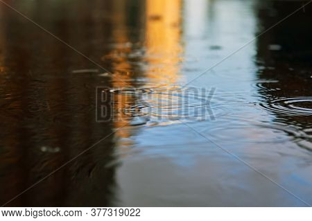 Drops Of Rain Bubbling In A Puddle With The Reflection Of Light