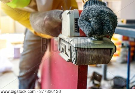 Carpenter Is Shaving Red Wood Door By His Shaving Machine In Outdoor Field With Steel Pole Building