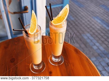Two Tropical Cocktails Adorned By Fresh Orange And Brightly Lit By Setting Sun On The Wooden Table O