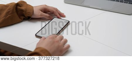 Female Hands Using Mock Up Smartphone On Worktable With Laptop In Home Office