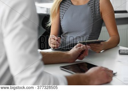 Cropped Head Of Man Using Touchpad And Woman Writing In Clipboard As They Are Working Together
