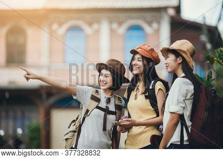 Asian Woman Group Backpacker Wearing Hat, Young Female Use Map In Mobile Phone For Travel, Friendshi