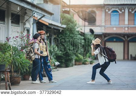 Asian Woman Group Backpacker Take A Photo With Friends On Street Together, Friendship Traveller Back