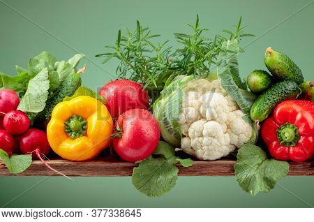 Various Fresh Raw Vegetables On A Green Background, Copy Space.  Cauliflower, Tomato, Cucumber, Radi