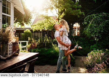 Beautiful And Happy Couple Having Fun In The Garden In The Courtyard. Honeymoon On Vacation.