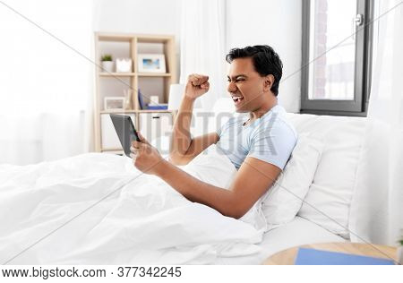 technology, bedtime and rest concept - happy smiling indian man with tablet pc computer lying in bed and making winning gesture at home