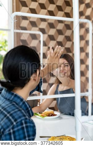 Asian young couple eating out together at new normal social distance restaurant with table shield partition reduce infection of coronavirus covid-19 pandemic. Restaurant new normal lifestyle.
