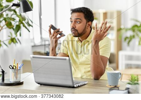 technology, communication and people concept - angry indian with smartphone and laptop computer using voice command recorder at home office