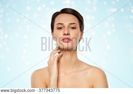 beauty, bodycare and people concept - beautiful young woman touching her neck over lights on blue background