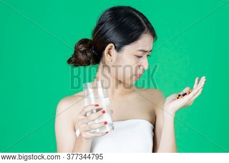 Anxiety Stressed Young Asian Woman Holding Pills On Hands Over Green Isolated Background. Medicine A