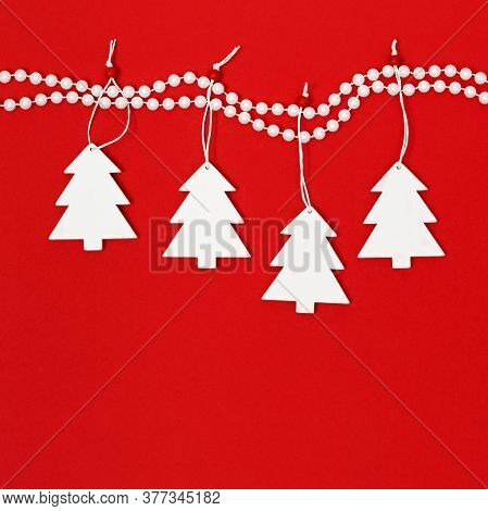 Composition Of White Christmas Trees Hanging On Decor Pearl Beads On Bright Red Background. Concept