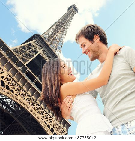 Paris Eiffel tower romantic couple embracing kissing in front of Eiffel Tower Paris France. Happy young interracial couple Asian woman Caucasian man. poster