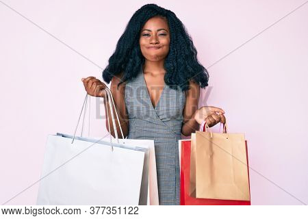 Young african american woman holding shopping bags puffing cheeks with funny face. mouth inflated with air, catching air.