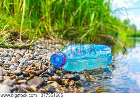 The Problem Of Environmental Pollution With Plastic. A Plastic Bottle Discarded On The Riverbank