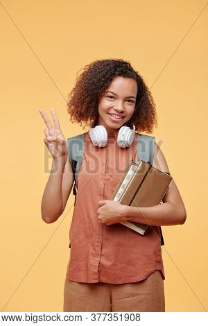 Portrait of cheerful cool African-American student girl in sleeveless shirt showing two fingers against yellow background