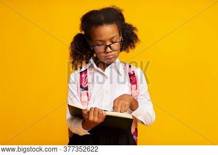 Dyslexia Concept. Black Schoolgirl Reading Book Standing Over Yellow Background. Studio Shot