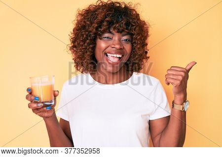 Young african american woman drinking glass of orange juice pointing thumb up to the side smiling happy with open mouth