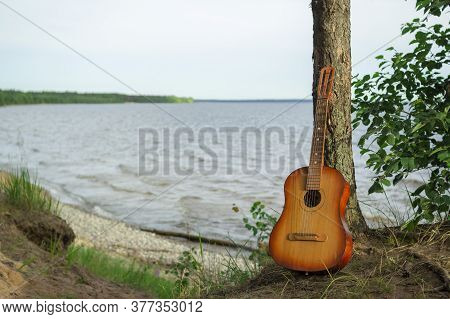 The Guitar Is Leaning Against A Tree, Against The Background Of The Lake.