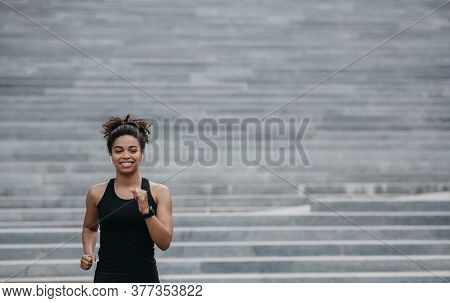 City Sport. Happy African American Girl In Sportswear With Fitness Tracker Runs Down The Stairs, Fre