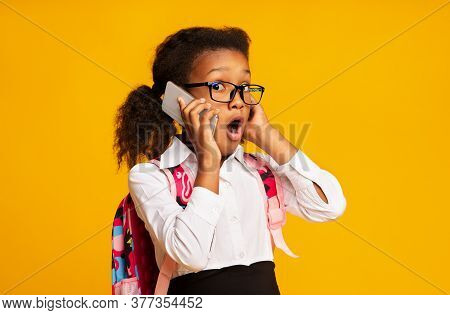 Oops. Shocked African Schoolgirl Talking On Cellphone Listening To Rumors Standing On Yellow Studio