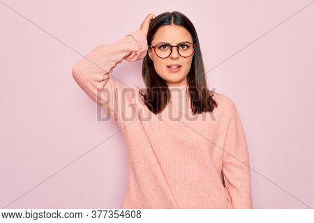 Young beautiful brunette woman wearing casual sweater and glasses over pink background confuse and wonder about question. Uncertain with doubt, thinking with hand on head. Pensive concept.