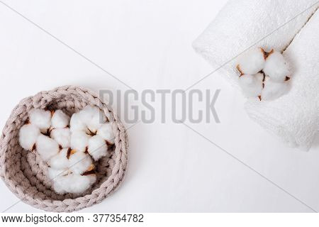 Spa Background. Fluffy Flower Of Cotton Plant In Box And White Cotton Towels On Light Concrete With
