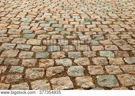 Natural Paving Granite On Road. Paving Stone In City.