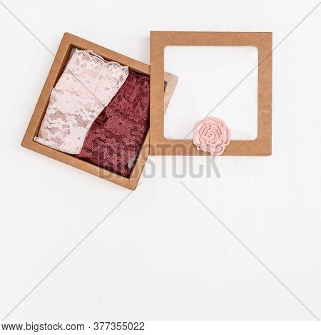 Womens Lingerie On Concrete Background With Copy Space. Two Lace Bikini Panties In Paper Box. Top Vi