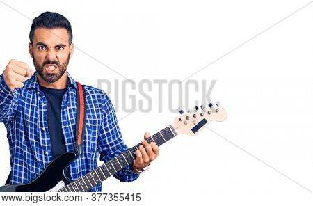 Young hispanic man playing electric guitar annoyed and frustrated shouting with anger, yelling crazy with anger and hand raised