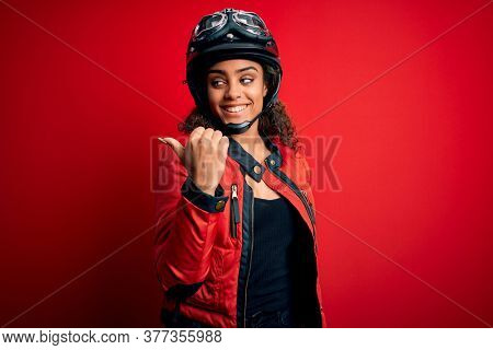 Young african american motorcyclist girl wearing moto helmet and glasses over red background smiling with happy face looking and pointing to the side with thumb up.