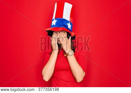 Young beautiful brunette woman wearing united states hat celebrating independence day rubbing eyes for fatigue and headache, sleepy and tired expression. Vision problem