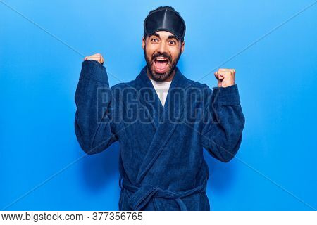 Young hispanic man wearing sleep mask and robe screaming proud, celebrating victory and success very excited with raised arms