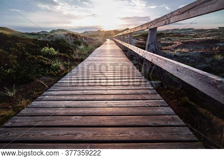 Deserted Wooden Boardwalk Leading Away Through Coastal Dunes Vegetation Towards A Glowing Cloudy Sun