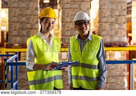 Portrait of asian warehouse manager and warehouse worker with clipboard to assign job with distribution warehouse in background. Reopening business warehouse technology and logistic concept.