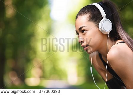 Closeup Of Motivated Asian Jogger Girl With Headphones Resting During Training At Park, Side View Wi